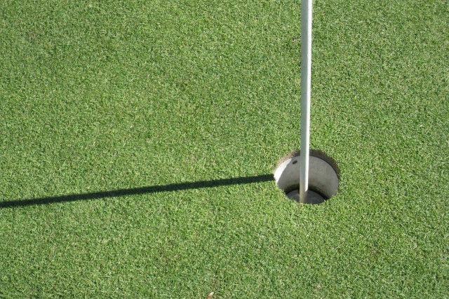 ゴルフのホールとフラッグから伸びている影